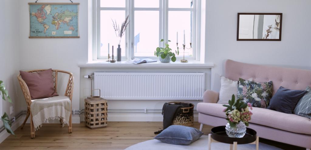 Bild på ett vardagsrum i en av våra lägenheter, på bilden ser man soffa, fönster och element.